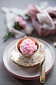 Pink carnation in vintage-style teacup with gilt edge