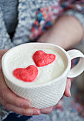 A woman wearing a mug of white hot chocolate with whipped cream and pink heart marshmallows