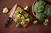 Frischer Broccoli mit Messer auf Holzschneidebrett und in Schale