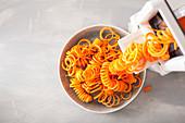 Möhrenspiralen mit einem Spiralschneider zubereiten