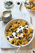 Pilaf with pumpkin, pumpkin seeds, prunes and yogurt