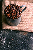 Metal mug with roasted coffee grains placed on cloth napkin on rough table