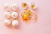 Osterstilleben mit aufgeschlagenem Ei, Goldglitter und bunten Sternchen