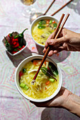 Hand holding a bowl of oriental ramen healthy noodles soup with shiitake, spinach, carrots, eggs and chillies