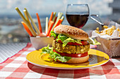 Homemade healthy vegan green lentil burger with tomato, lettuce and french fries with glass of red wine