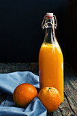 Bottle of fresh citric orange juice placed near fresh oranges