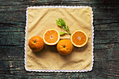 Halves of fresh oranges on a wooden dark rustic table on a dark background
