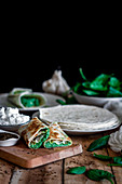 Tasty tortilla stuffed with puree of spinach on wooden table with ingredients