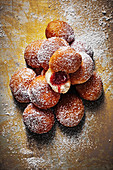 A stack of mini jam doughnuts with icing sugar