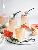 Three glasses of grapefruit cocktail on a marble tray with rosemary and grapefruit slices