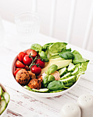 A salad bowl with falafel, cucumber, avocado and tomatoes
