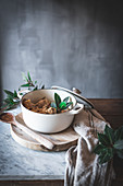 Stewed chicken with broth in pan decorated with green leaves on white marble table