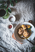 Stewed chicken drumsticks with broth in white ceramic bowl