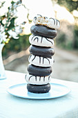 Yummy donuts with icing and chocolate ganache stacked on plate