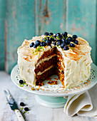 Layered carrot cake with buttercream icing and blueberries