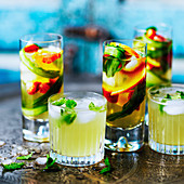 Cocktail with mint and ice and cocktail with cucumber, fruits and strawberries