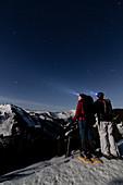 Schneeschuhwanderer im Mondlicht auf den Höhen bei Bolsterlang im Allgäu, Deutschland