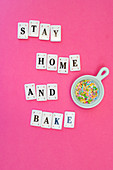 The words Stay Home And Bake with colourful sugar sprinkles