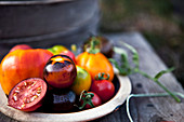 Various tomatoes in a bowl on a wooden background