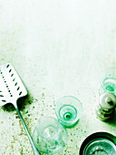 Utensils (Spatula, glasses, pepper mill) on green surface