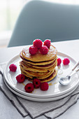 Stack of tasty pancakes with ripe raspberries