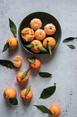 Fresh peeled tangerines and unpeeled fruits with green leaves