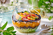 Layered black rice salad with vegetables and oranges