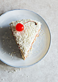Slice of coconut cake with a glacier cherry on top