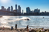 A view of the Brooklyn Bridge with a couple on the river bank, New York City, USA