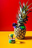 Ananas mit Sonnenbrille davor Schneekugel mit Mini-Palme