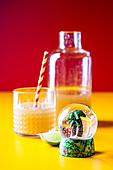 Eistee mit Ananas und Kokossirup davor Schneekugel mit Mini-Palme