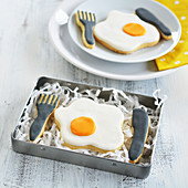 Fried egg and cutlery biscuits in a tin and on a plate