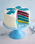 A rainbow cake decorated with a unicorn