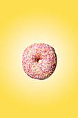 Donut mit rosa Zuckerglasur und Zuckerstreuseln