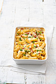 Rigatoni casserole with cooked ham, broad beans and mozzarella