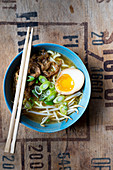 Ramen soup with beef, spring onions, sprouts and an egg