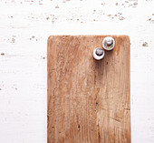 Salt and pepper on a wooden cutting board