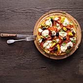 Spaghetti pizza with tomatoes, sausage and mozzarella