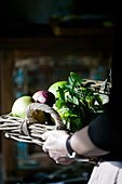 Holding wicker tray of fruit and herbs
