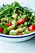 Pasta salad with pesto, arugula, tomatoes and mini mozzarella