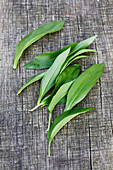 Several wild garlic leaves on a wooden surface