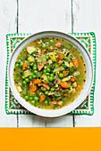 Vegan vegetable soup with peas and smoked tofu