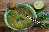 Salsa Verde in a green ceramic bowl with a wooden spoon