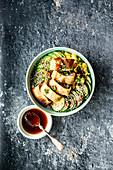 Asia bowl with spring rolls and sweet and sour sauce
