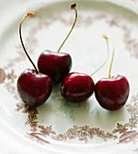 Rote Kirschen auf Porzellanteller (Nahaufnahme)
