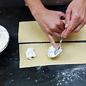 Preparing stuffed pasta: place the filling on the dough sheet