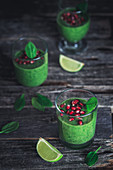 Green spinach smoothie with pomegranate seeds