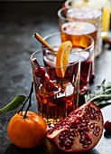 Various alcoholic drinks with whisky, bourbon, vodka, cranberry, oranges, pomegranates, rosemary and thyme