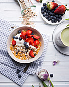 Muesli with almond yogurt and fresh berries, with matcha tea
