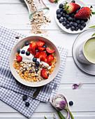 Muesli with almond yogurt and fresh berries, with matcha tea